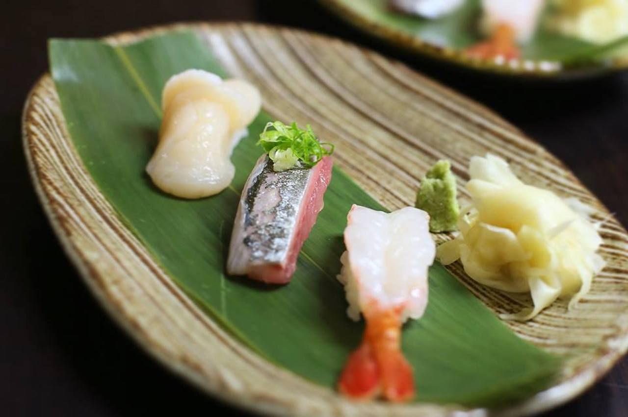 trio of sushi on a leaf with ginger and wasabi