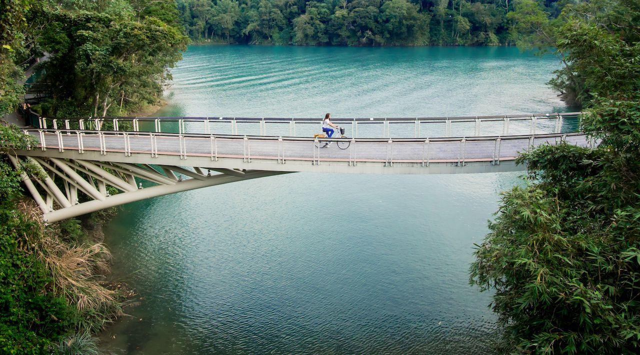 Young girl riding bicycle on the bridge at Sun Moon Lake, Nantou, Taiwan