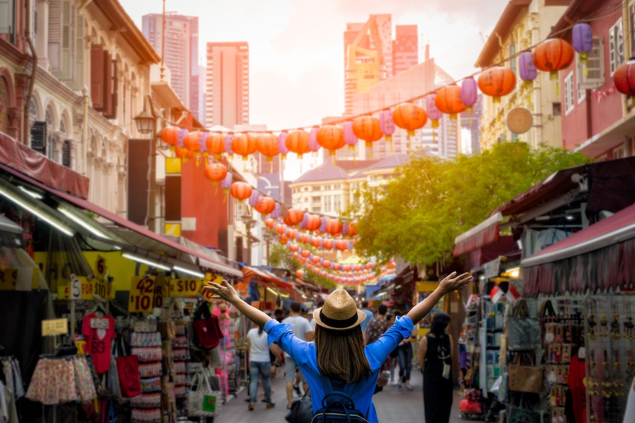 Young woman traveler with backpack and hat traveling into Chinatown at singapore