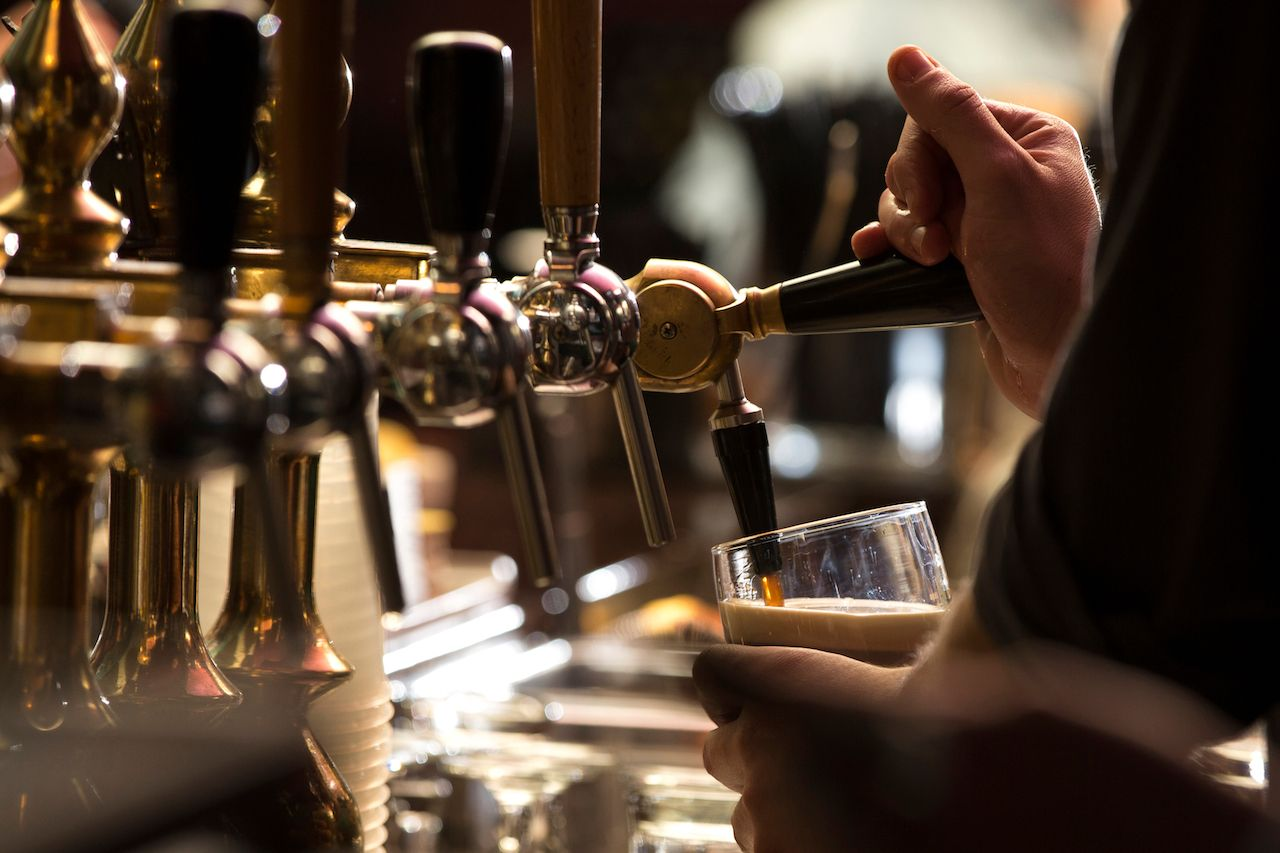 closeup of a bartender pouring a dark stout beer