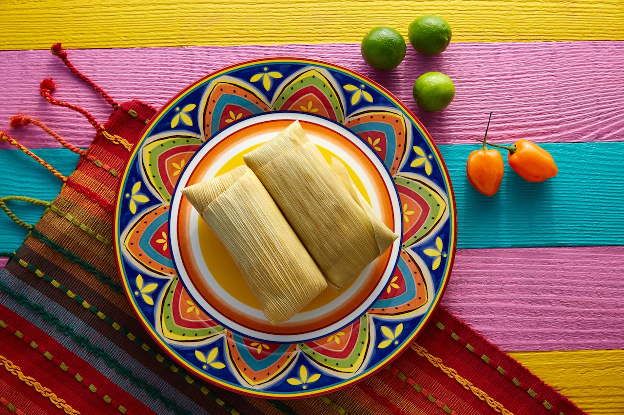 tamales on a colorful plate on top of a woven mat and brightly striped