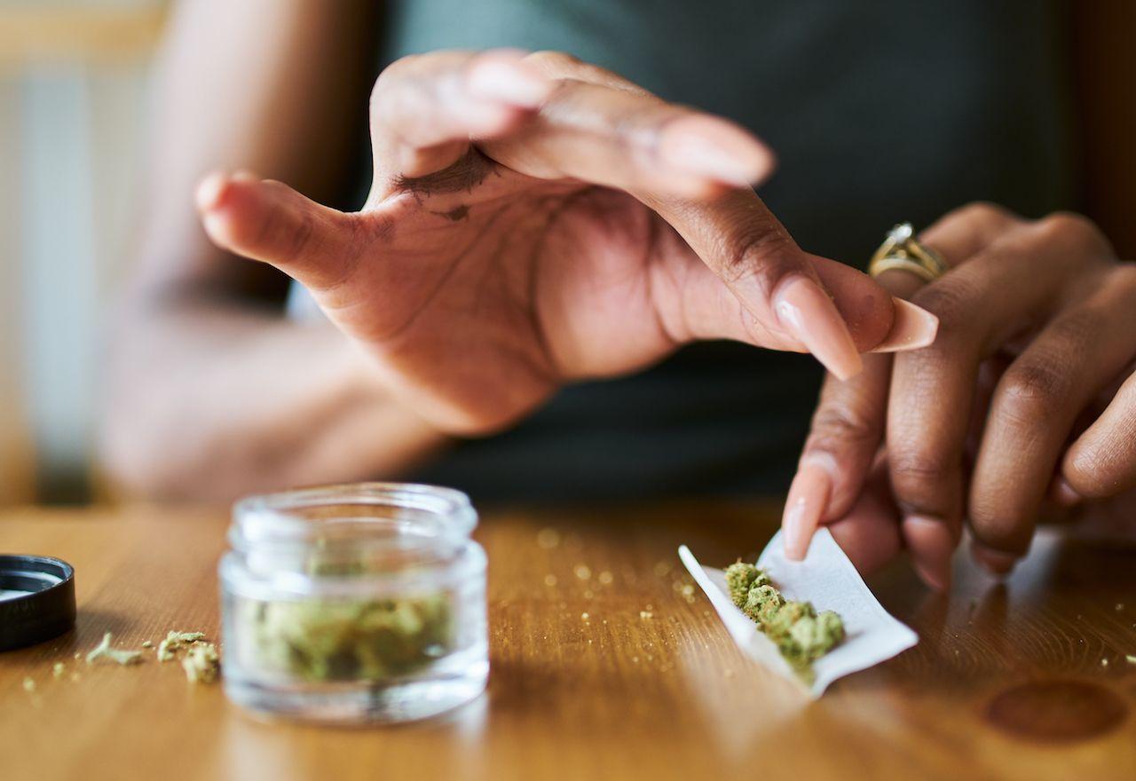 woman at home rolling marijuana