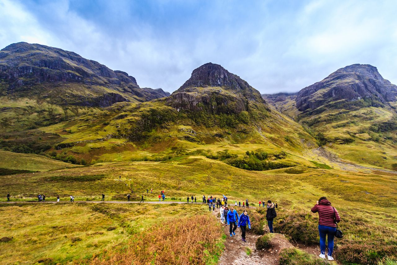 A beautiful view of Glencoe with tourists, the famous tourist attraction of Scottish Highland