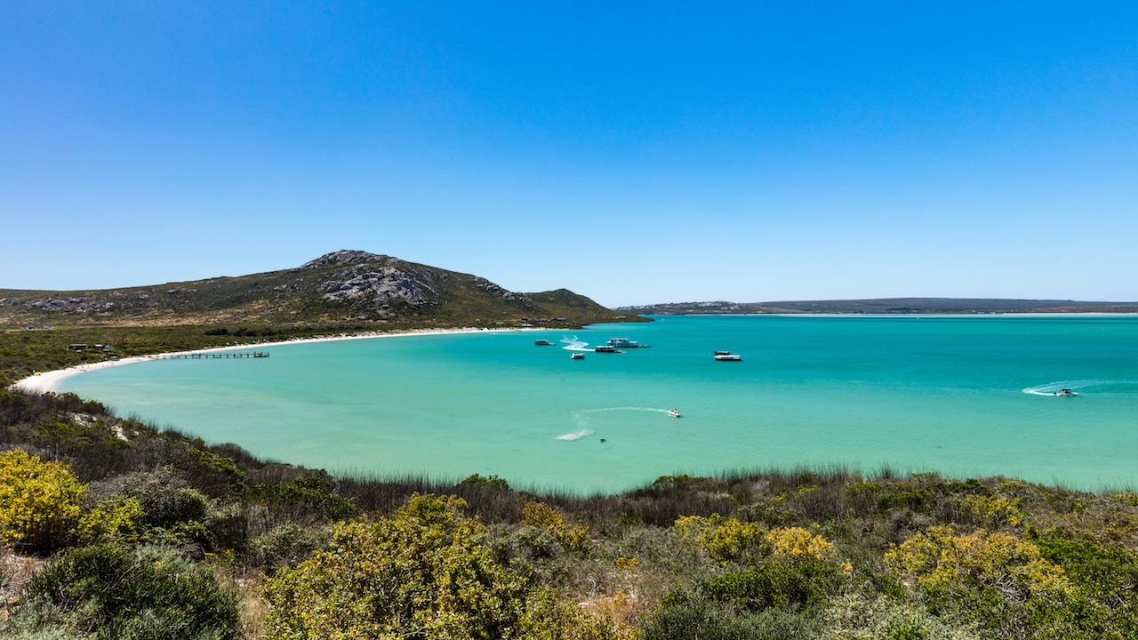 A scenic view of the turquoise waters of the Langebaan Lagoon at Kraalbaai with houseboats and other boats in the water with a clear blue sky