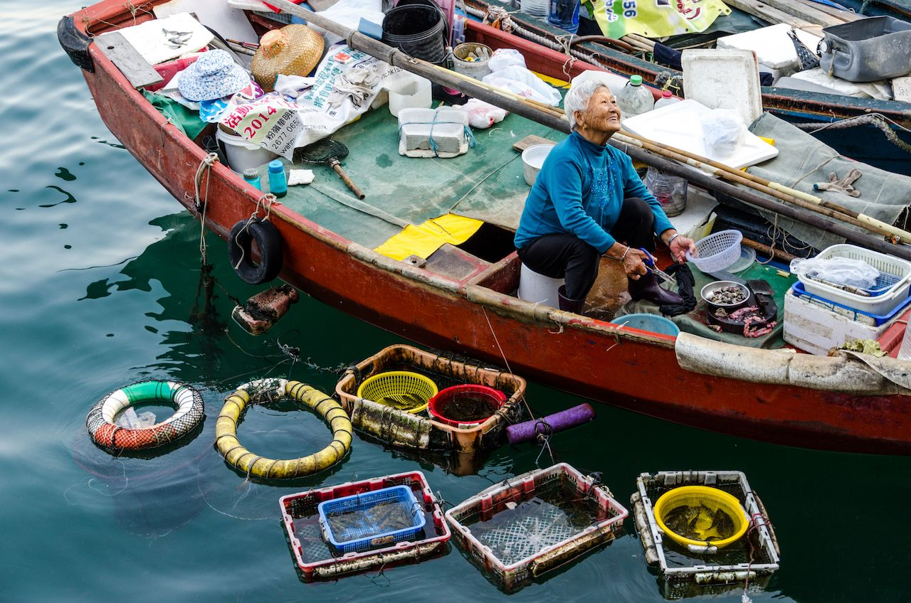 An unidentified old woman sells seafood in her boat