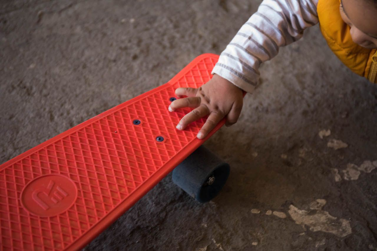 Baby playing with a mini skateboard