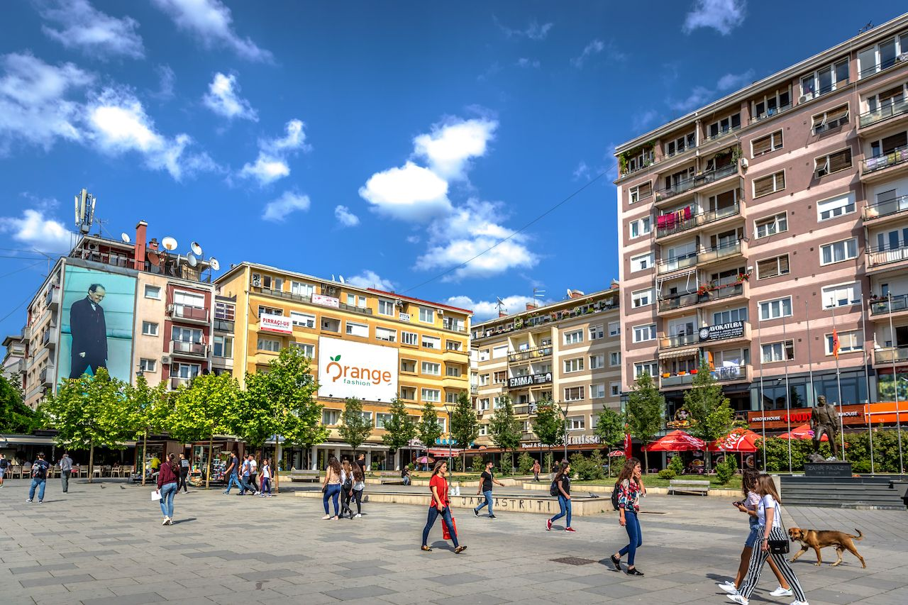 Big group of people walking in front of colorful buildings in a blue skies day in Kosovo