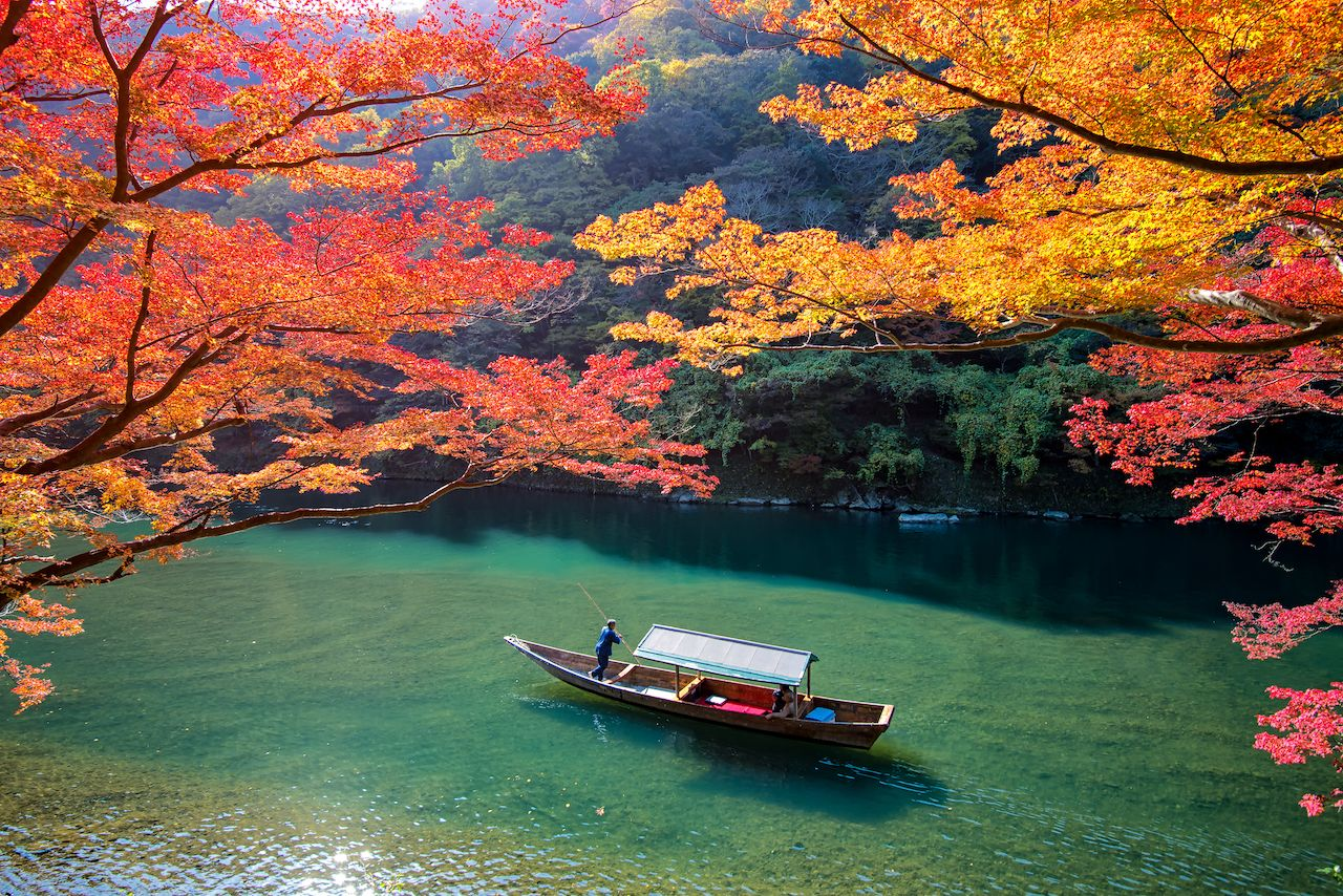 Boatman punting the boat for tourists to enjoy the autumn view along the bank of Hozu river in Arashiyama Kyoto, Japan