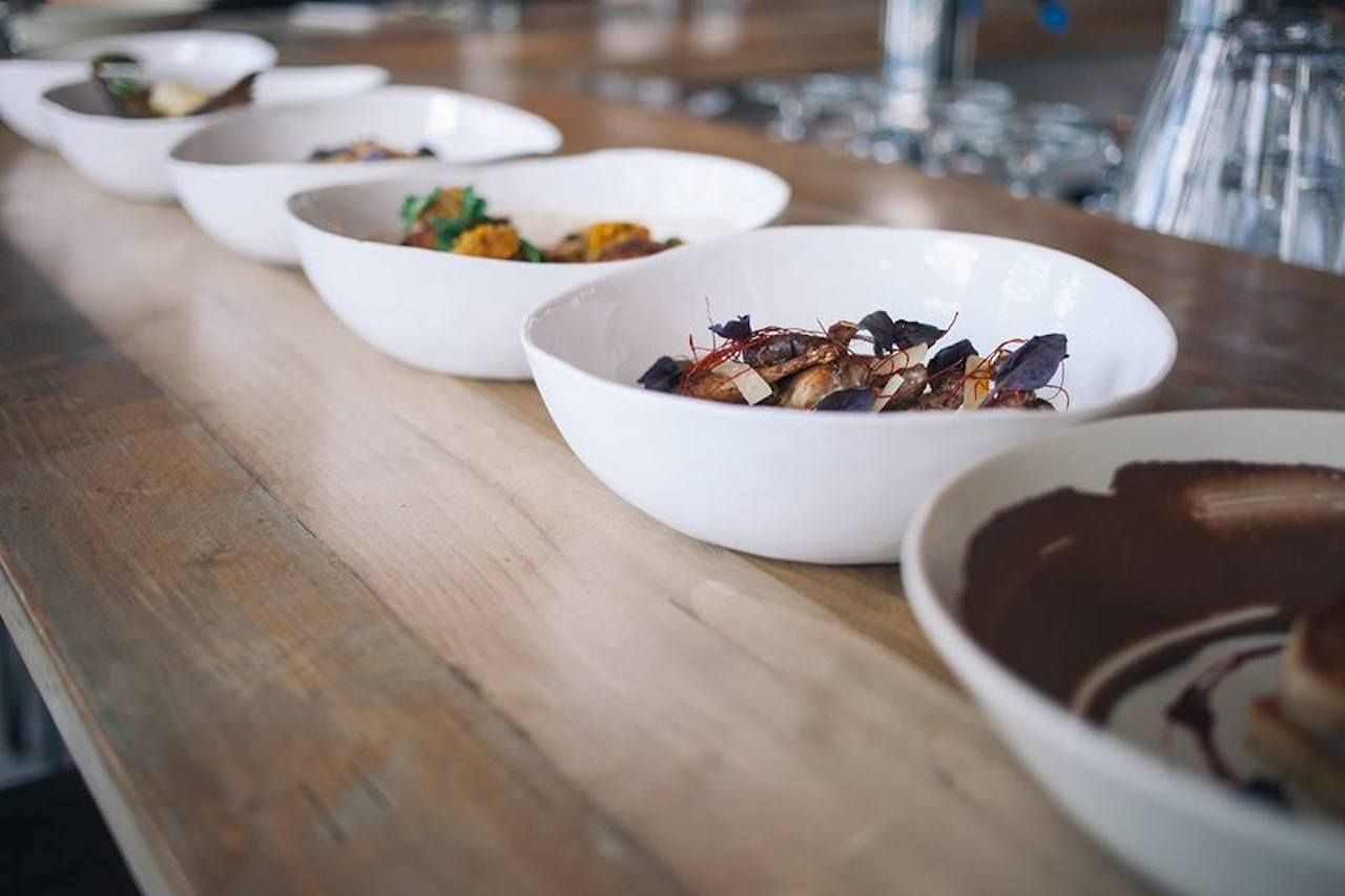 Bowls of artfully plated food on a wooden table