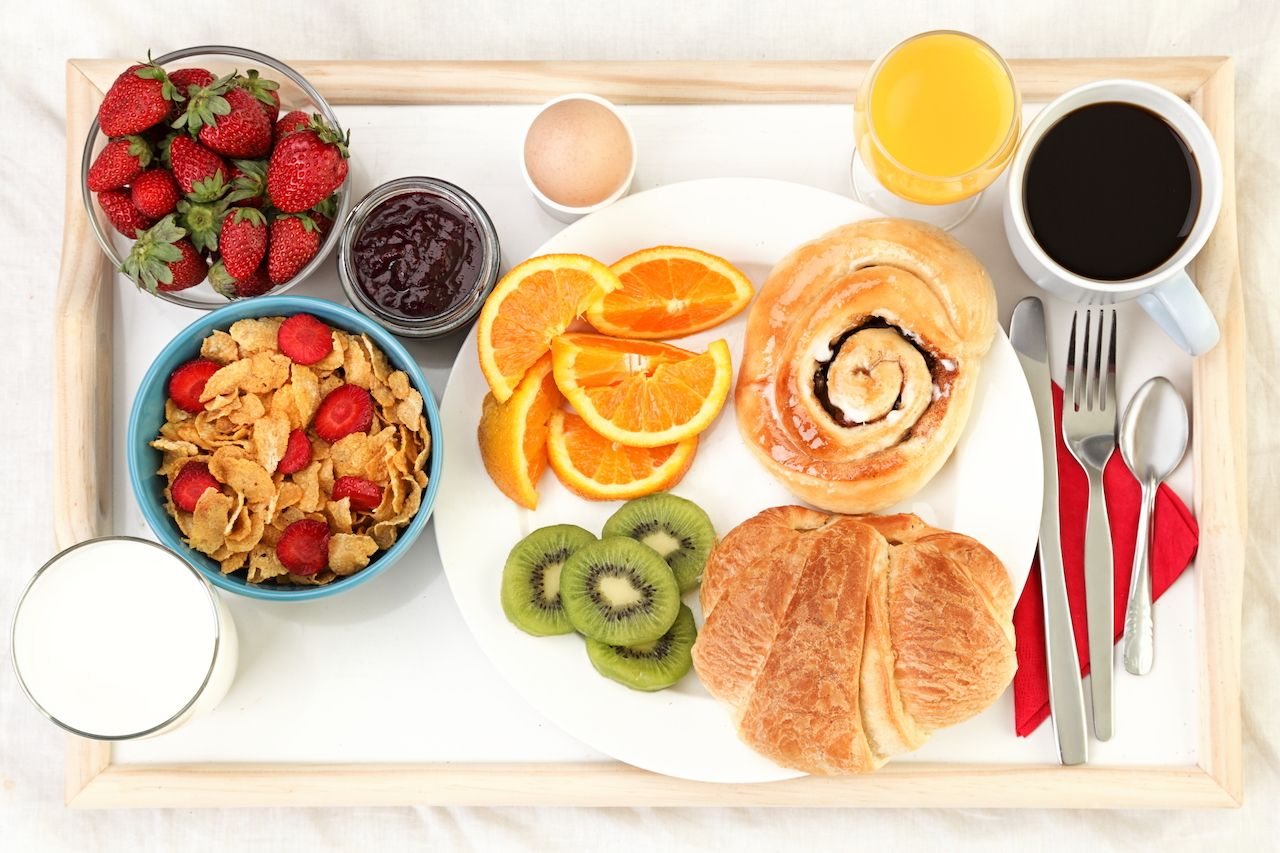 Breakfast tray in bed with coffee, bread, cereals, fruit
