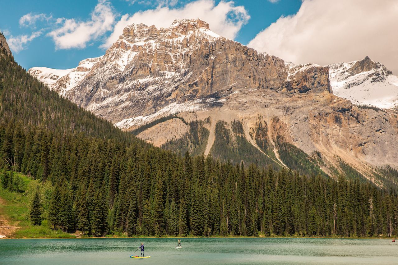 Canadian landscape, with turquoise water lake, pine forest and Rocky Mountains
