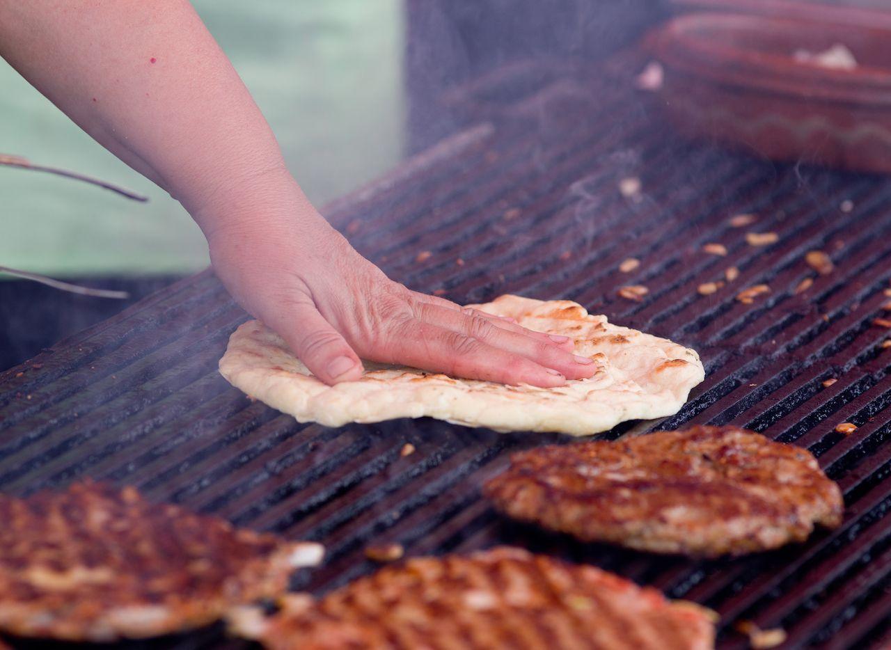 Close up of traditional Balkan food, burgers and flat bread on barbecue