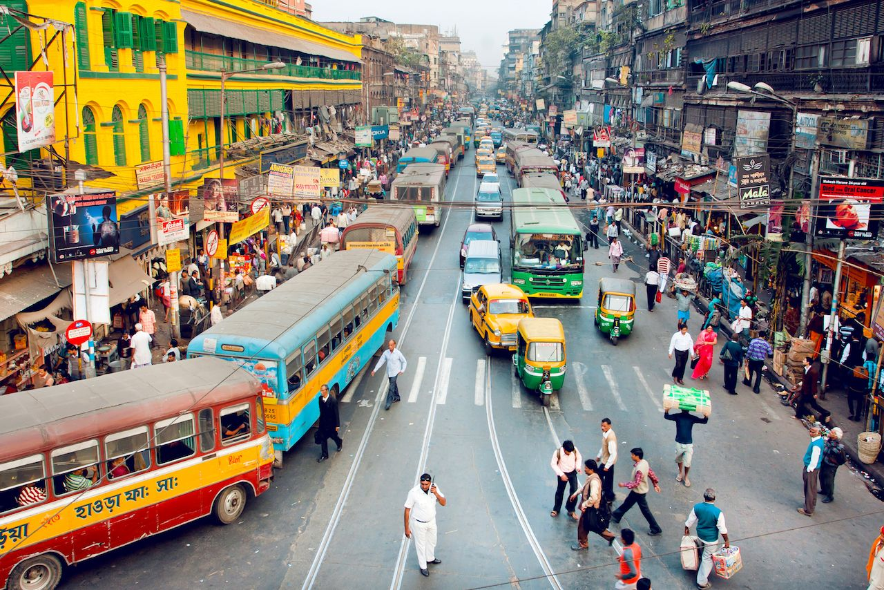 Crowd of people, buses, and cars in Kolkata, India
