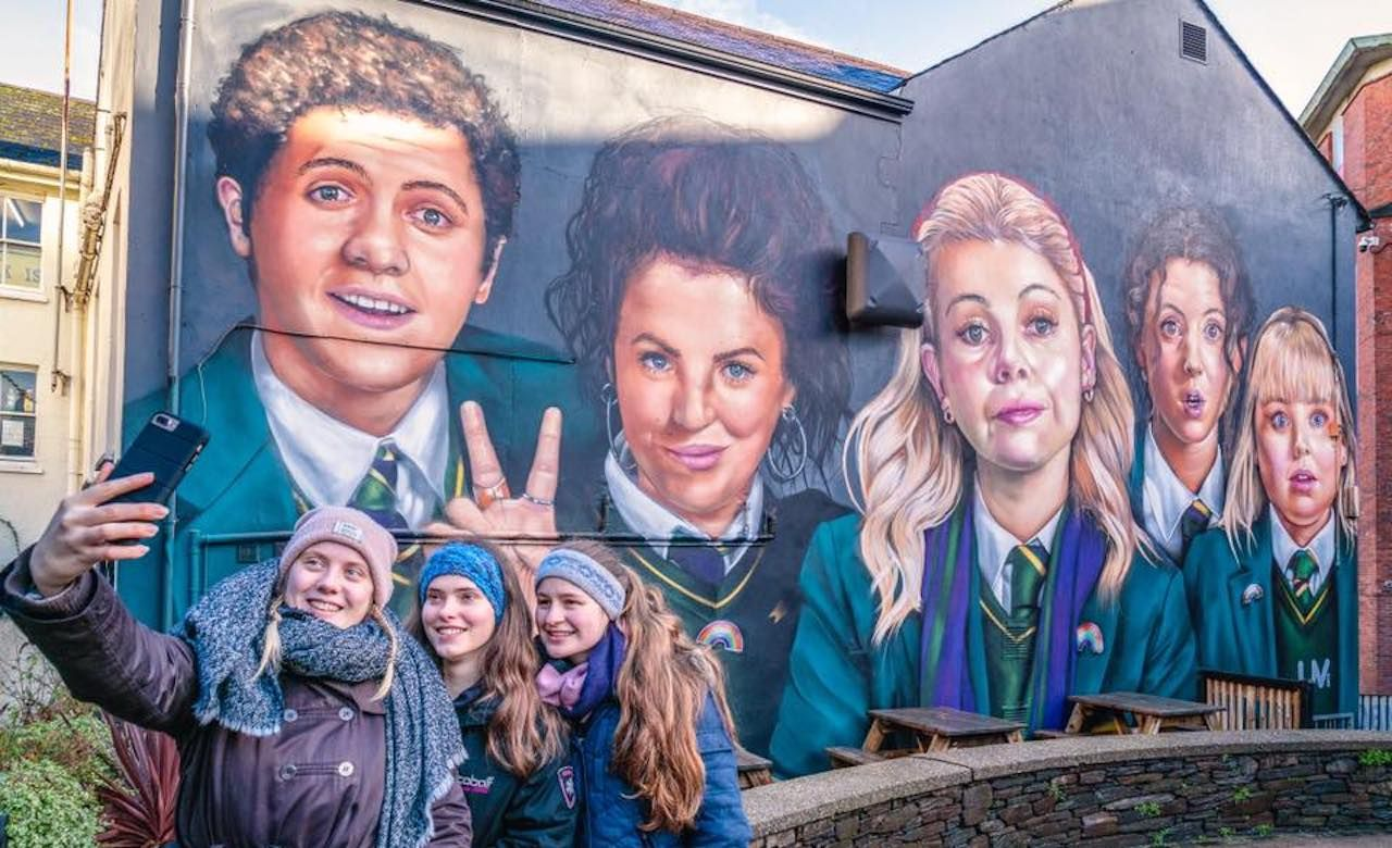 Fans taking a photo with Derry Girls mural in Derry, Northern Ireland