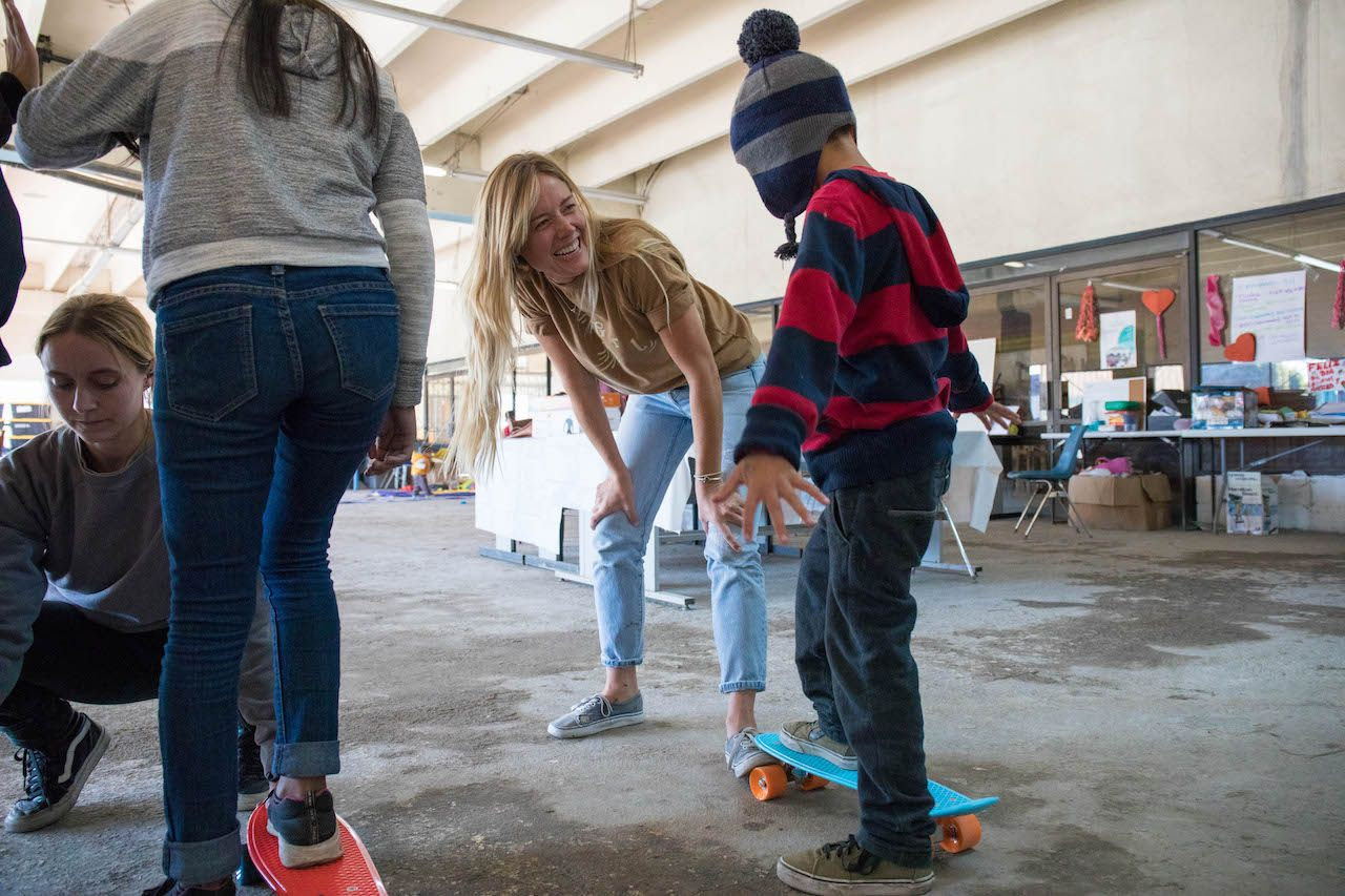 Female skateboarders teaching skateboarding to Mexican migrant kids