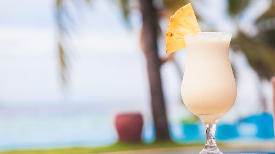 Glass of delicious pina colada cocktail by the sea