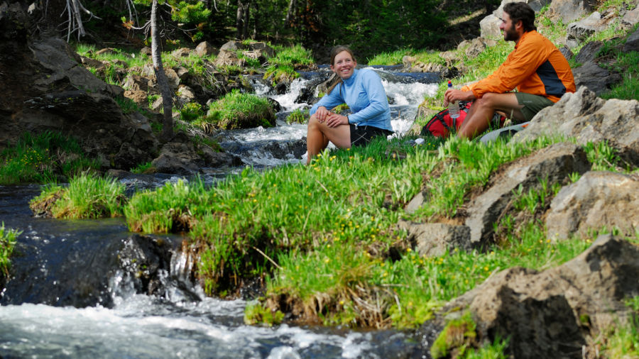 Hiker couple resting by a cold mountain stream Bend, Oregon, United States