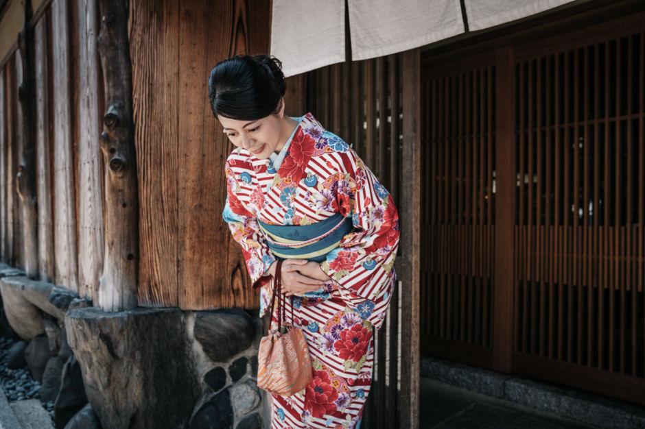 Japanese woman bowing wearing a kimono