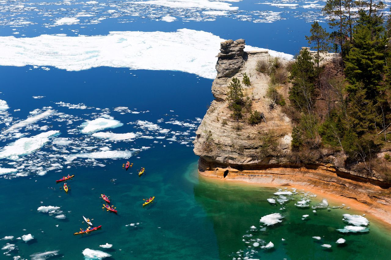 Kayaks maneuver through ice floes to view Miners Castle on Lake Superior