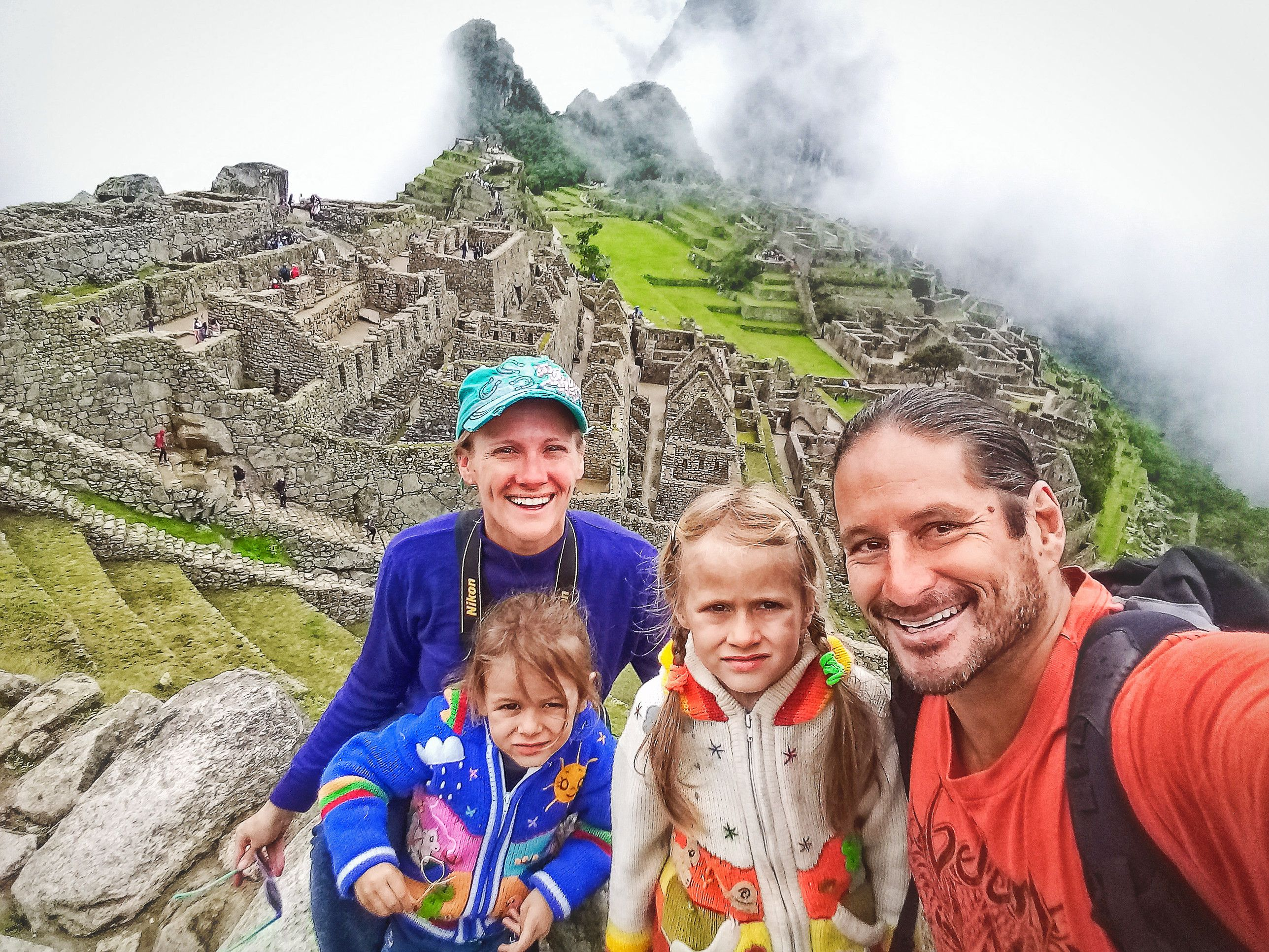 Family taking a selfie in front of Machu Picchu in Peru