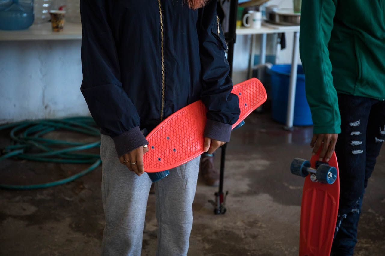 Mexican migrants holding skateboards