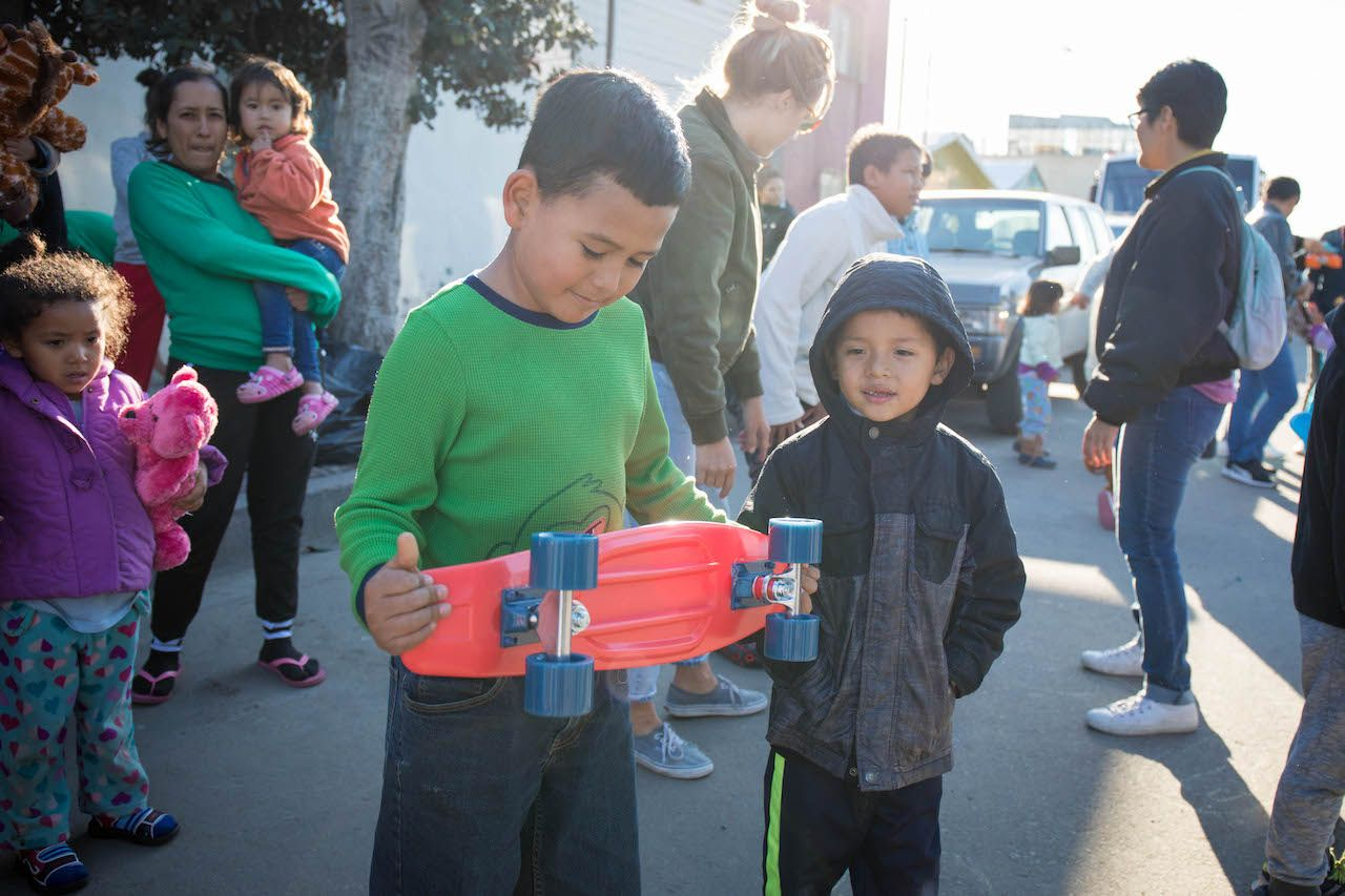 Migrant kids holding a skateboard with onlookers