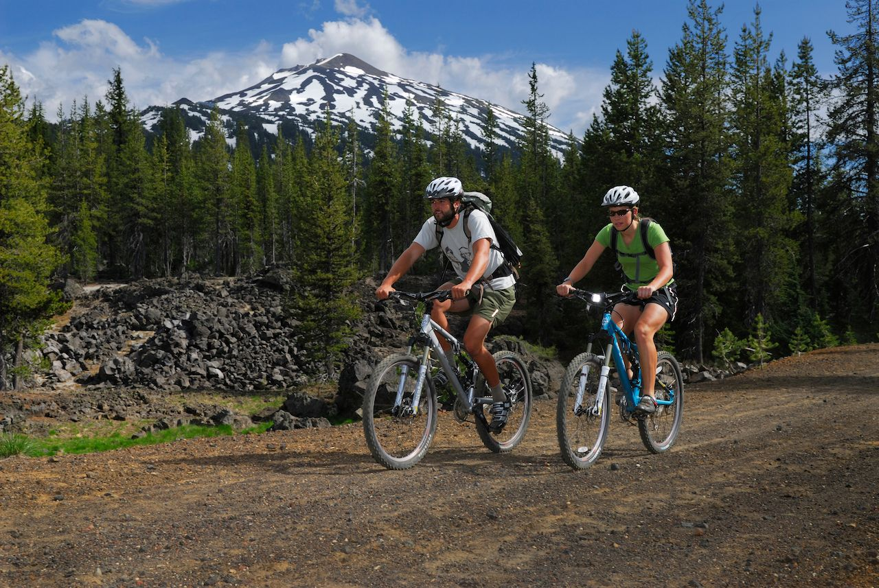 Mountain bikers traveling on dirt road under Bend Mount Bachelor, Oregon, United States