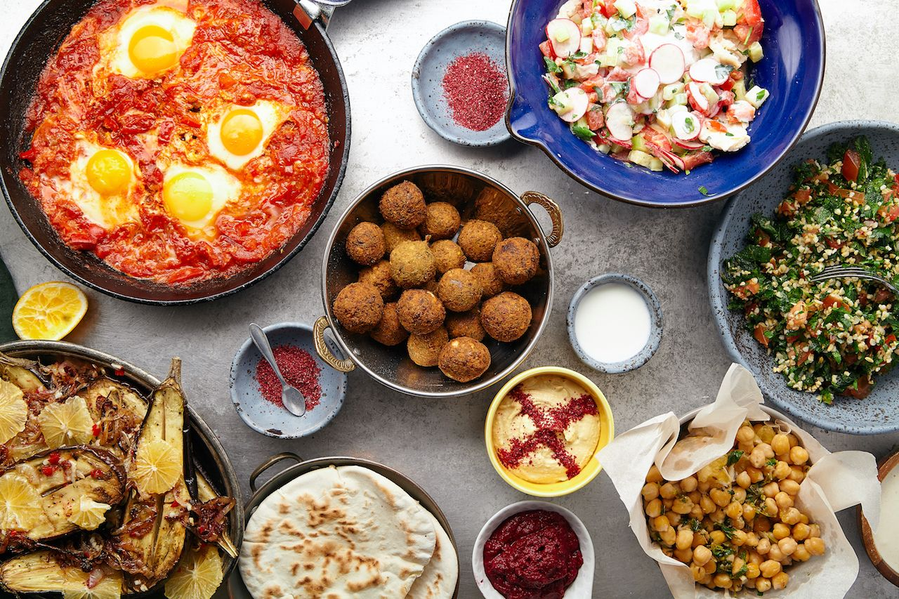Overhead image of traditional jewish and middle eastern food: falafel, fattoush, tabouli, shakshuka, balila, hummus, roasted eggplants and spicy beetroot dip