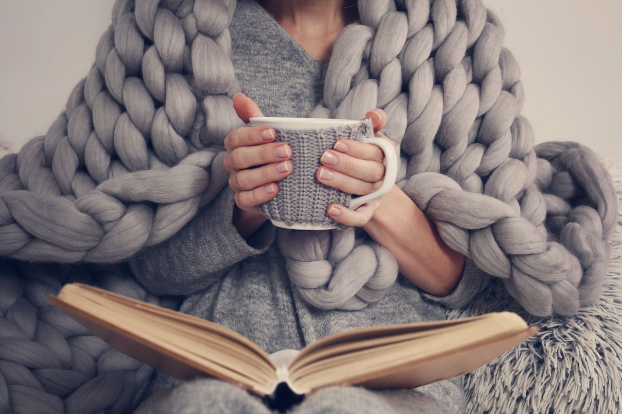 Person holding a mug with a book open