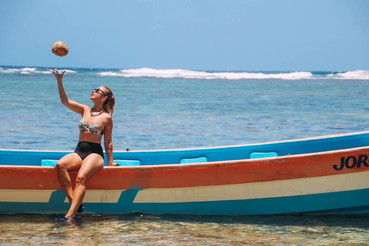 Solo female traveler throwing a coconut on a boat