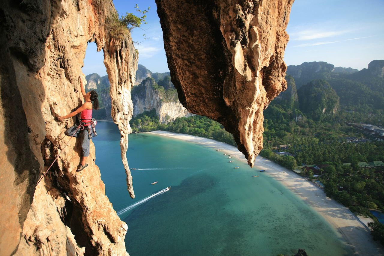 Stunning beautiful female professional climber rock climbing mountain multi pitch in Thailand cliff