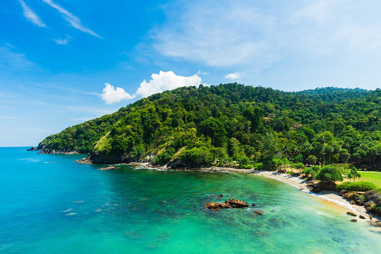 Summer beach with clear sea, green forest and blue sky on Koh Lanta island in Thailand
