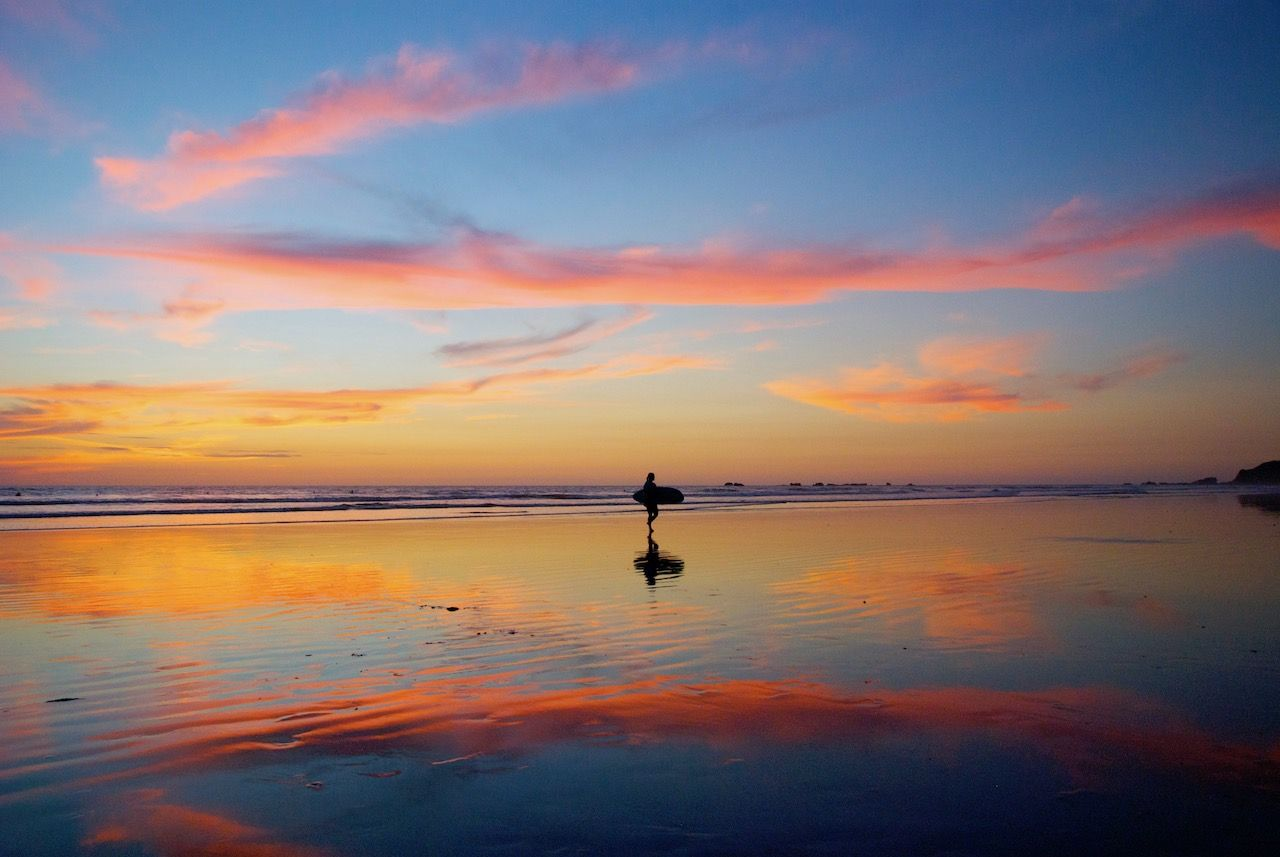 Surfer walking on the beach after sunset