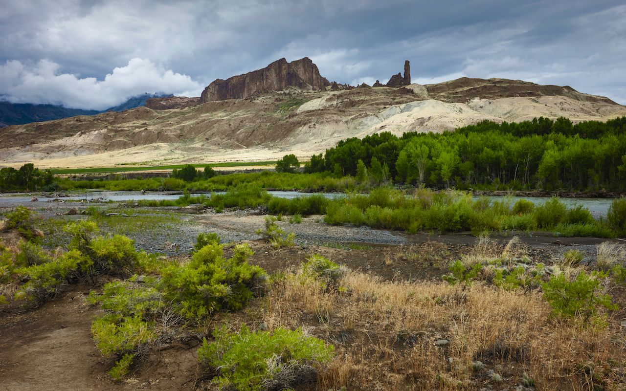 The arid landscape of the meadow with glimpse of Shoshone river and foothills of the Rocky Mountains on a late summer day near Cody, Wyoming