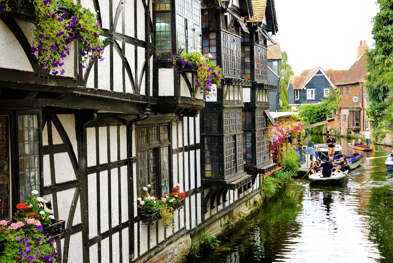 Tourist enjoying punting guided-tour in the heart of old Canterbury
