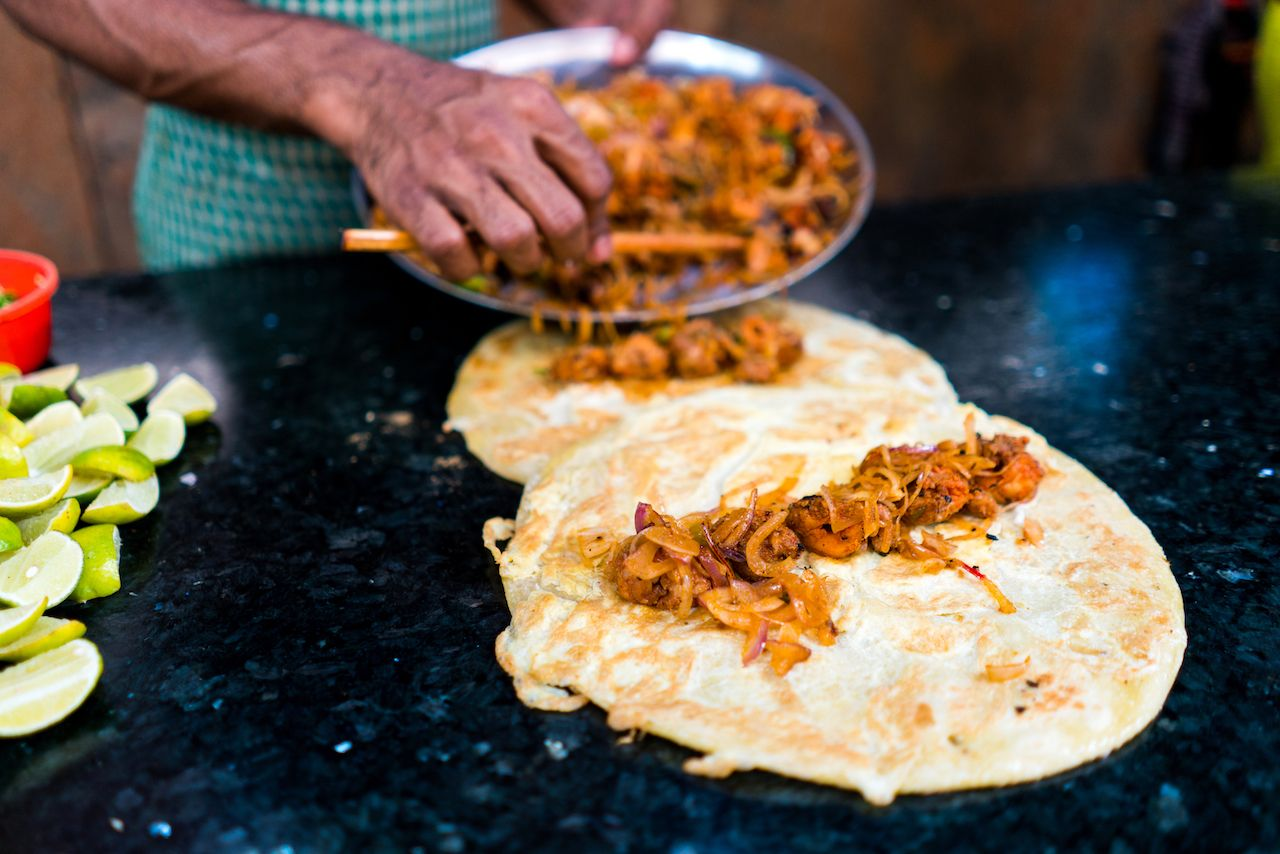 Two chicken and egg kathi rolls with onions being prepared on a blackboard with green limes by a street food vendor in Kolkata