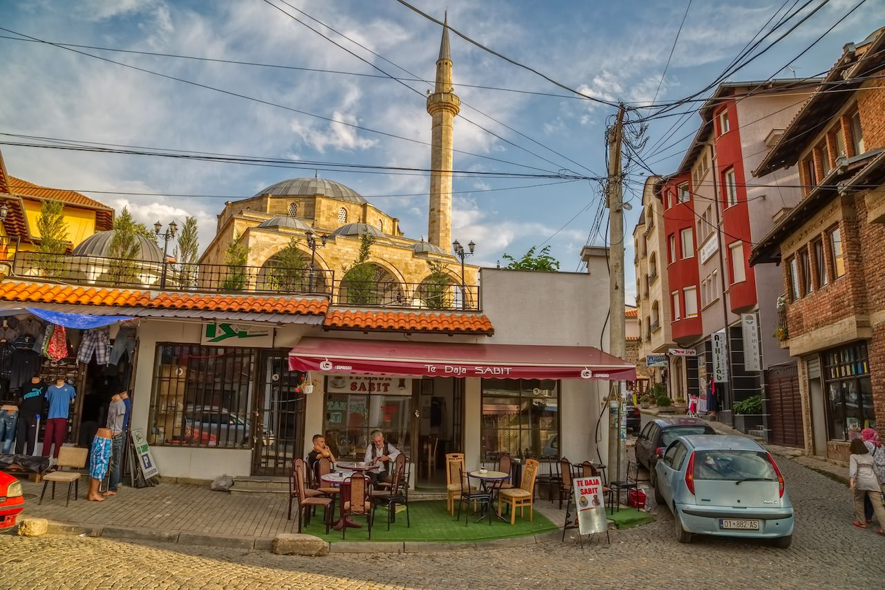 Two men resting with coffee under Fatih Mosque