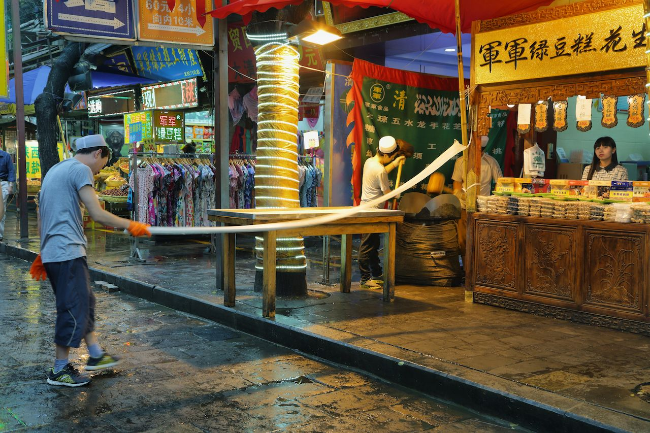 Unidentified man making handmade pasta in a food store on a rainy day in the Muslim Quarter of Xian, China