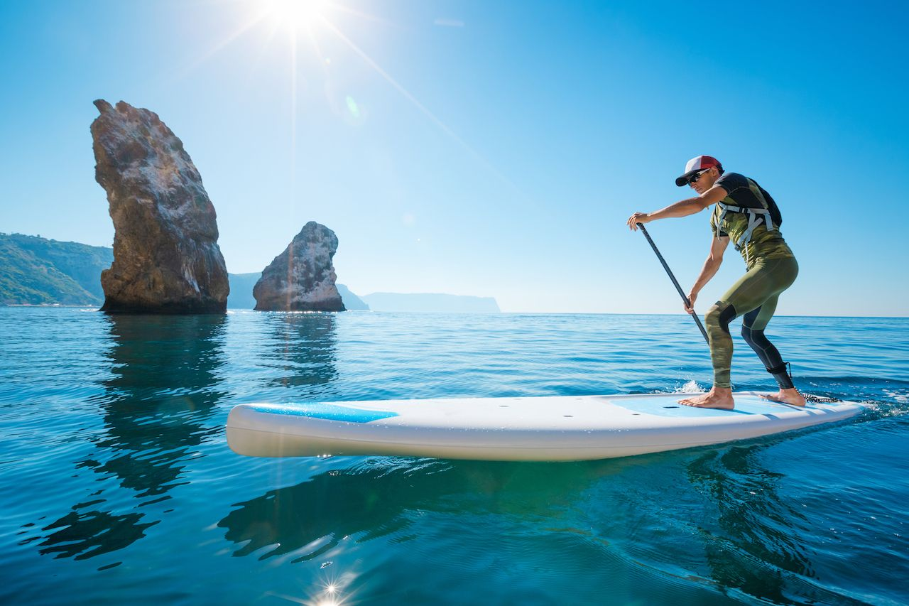 Young man is floating on a SUP board