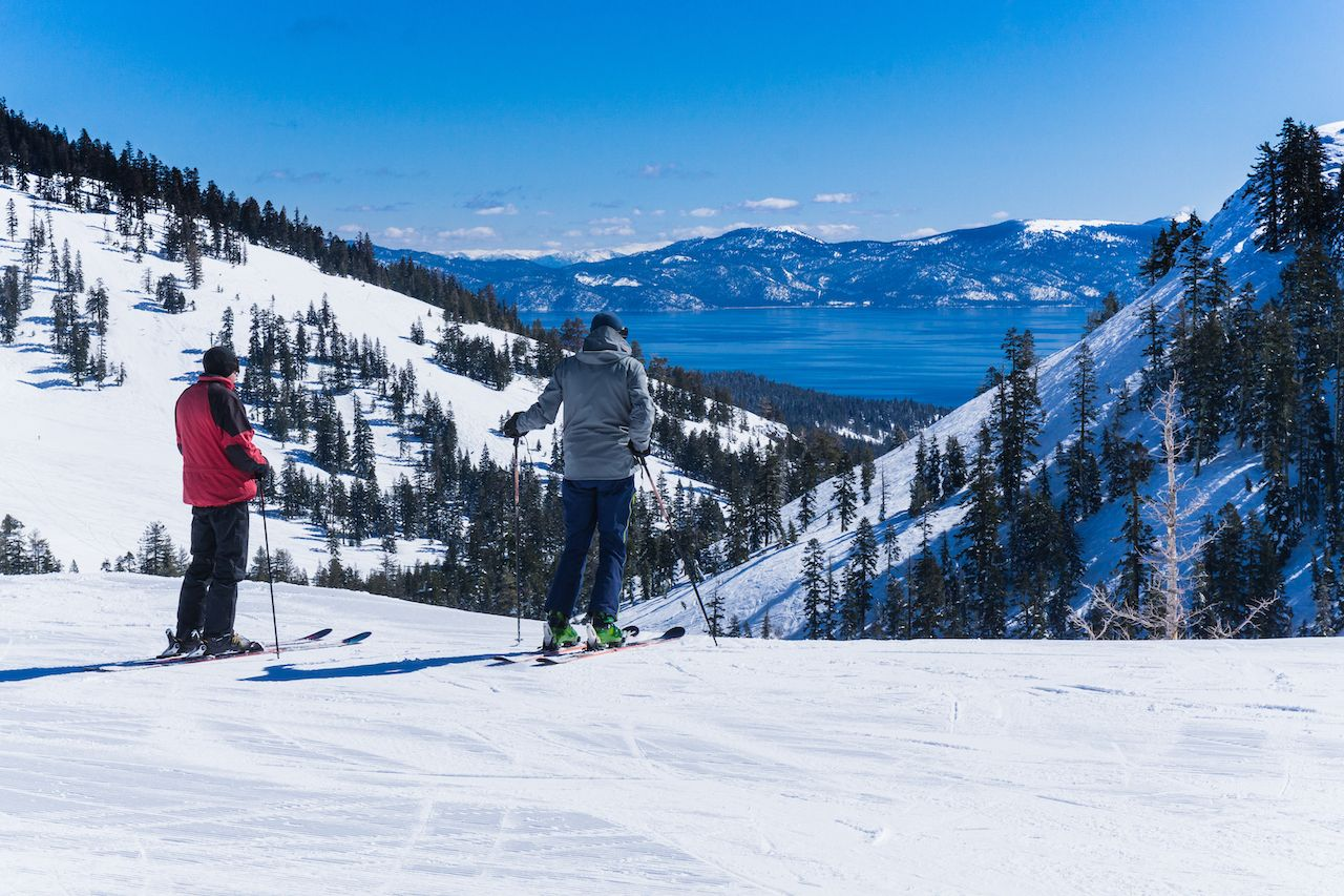 men on skis look out over the lake tahoe mountains