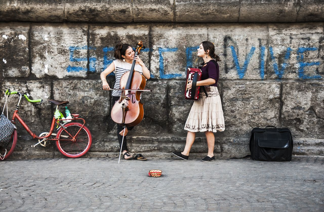two young musicians play music on the street in Naples