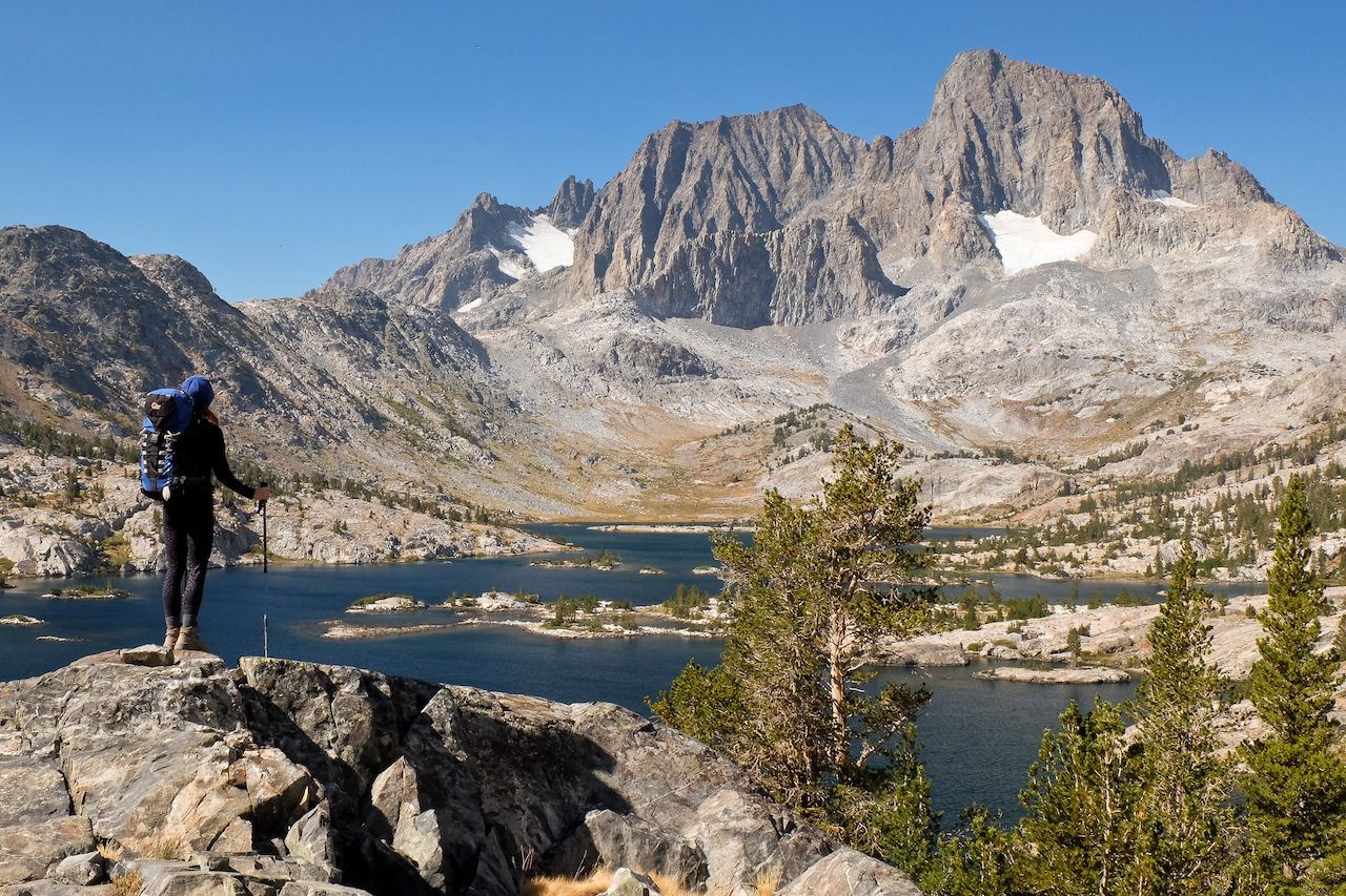 A Woman Hiker Stands High Above Garnett Lake in the Sierra Nevada