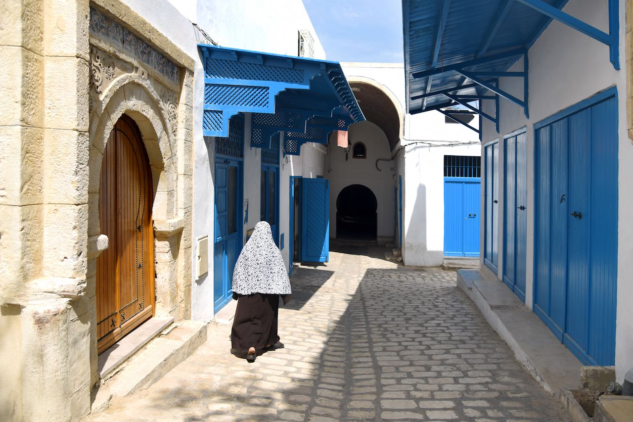 A woman in traditional Muslim clothing goes through the Old town of Sousse