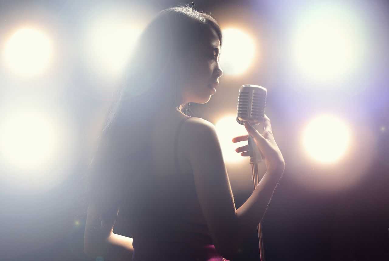 Asian woman singer holding a singing microphone