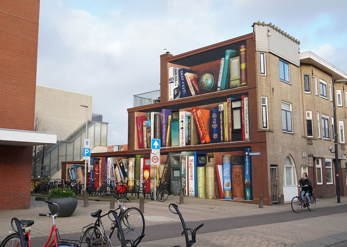 Street artists turn anonymous building into an amazing bookcase illusion