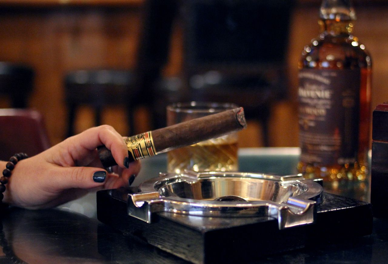 Churchill Bar in Denver, woman smoking cigar