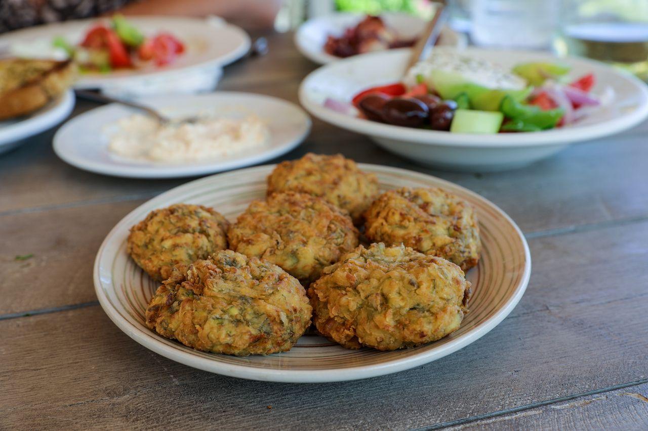 Fried zucchini balls plate near greek salad dish