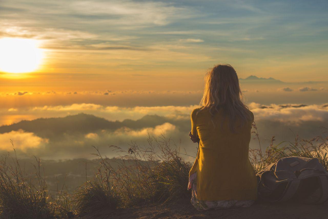 Girl watching the sunrise from Mount Batur, Bali