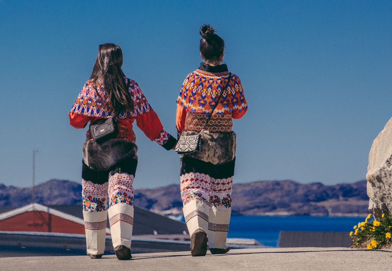 Greenland Nuuk Fjord women holding hands in traditional dress
