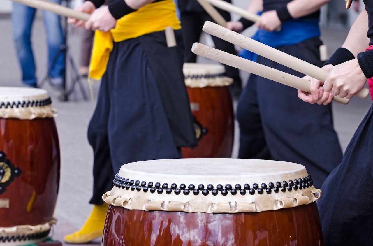 Group of japanese musicians playing on traditional japanese percussion instrument Taiko gold Wadaiko drums